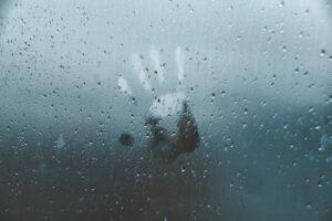 Hand against rainy window